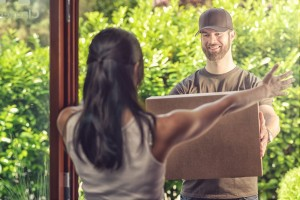 Woman taking delivery of a large parcel holding out her arms to the smiling friendly deliveryman as he hands it over, view from behind over her shoulder